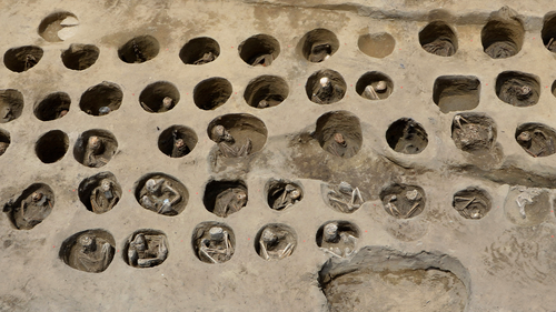 "This undated photo provided Wednesday, Aug. 26, 2020, by Osaka City Cultural Properties Association shows human bones buried in holes at the south section of the ""Umeda Grave"" burial site, in Osaka, western Japan."