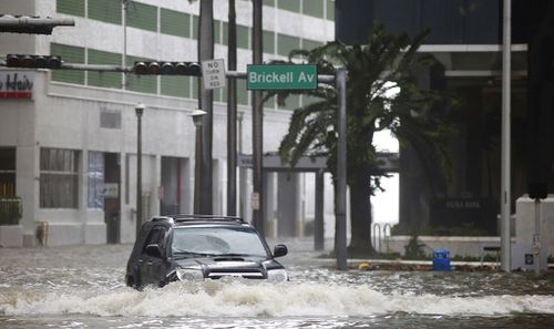 A vehicle drives on flooded Brickell Avenue in Miami. (AP)