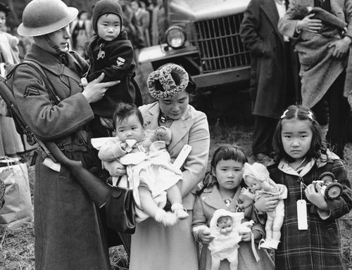 In this March 30, 1942 file photo, Cpl. George Bushy, left, a member of the military guard which supervised the departure of 237 Japanese people for California, holds the youngest child of Shigeho Kitamoto, center, as she and her children are evacuated from Bainbridge Island, Wash. (AP)