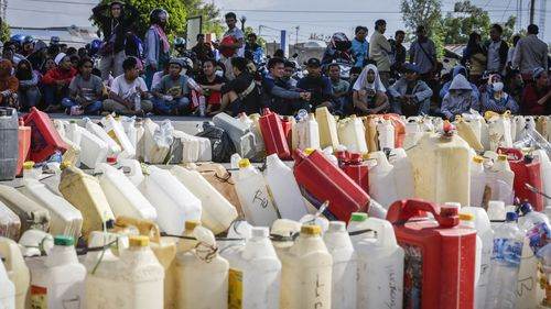 People sit as they queue for fuel at a gas station in Palu, Central Sulawesi, Indonesia after the powerful earthquake and tsunami.