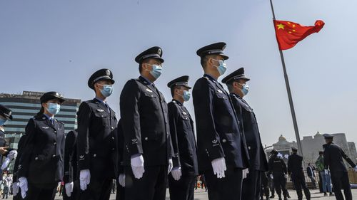 Chinese police officers wear protective masks as they stand in formation next to a national flag at half staff just before three minutes of silence to mark the country's national day of mourning for COVID-19