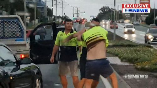 Two tradesmen were filmed on a dash cam throwing punches towards another driver, who fell to the ground twice.