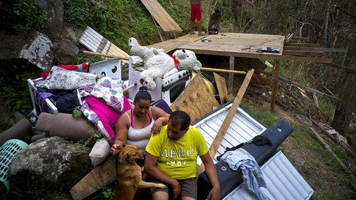 Yadira Sortre and William Fontan Quintero pose to what is left of their belongings, destroyed by Hurricane Maria while their children build a room to protect themselves from the elements, in the San Lorenzo neighbourhood. (AAP)