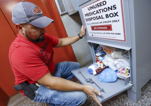 Narcotics detective Paul Laurella retrieves unused medications from the police department's disposal box in Barberton, Pennsylvania.