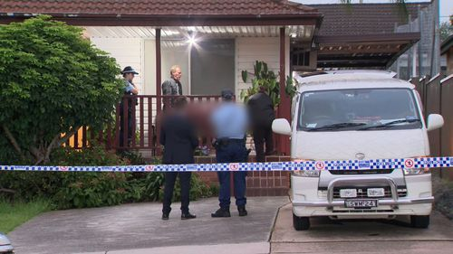 Police remove the body of a woman from the premises at Merrylands.