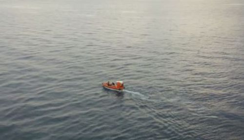 A person on the Sun Princess tweeted a picture of a small rescue boat speeding away from the cruiseliner. (Supplied)