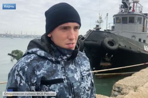 One of the three captured Ukrainian sailors shown on Russian state TV in front of a seized naval ship.