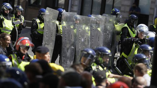 British police officers in riot gear scuffle with members of far-right groups protesting against a Black Lives Matter demonstration, in central London, Saturday, June 13, 2020.