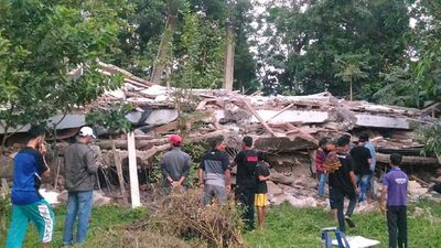 <p>Residents gather around a collapsed building in Pidie. </p> <p>(AFP)</p>