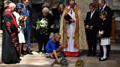 Lucy Hawking lays flowers as the ashes of her father, Professor Stephen Hawking, are laid to rest during his memorial service at Westminster Abbey. Picture: Ben Stansall/PA via AP