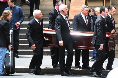 Angus watches the pallbearers place the casket in the hearse. Picture: AAP