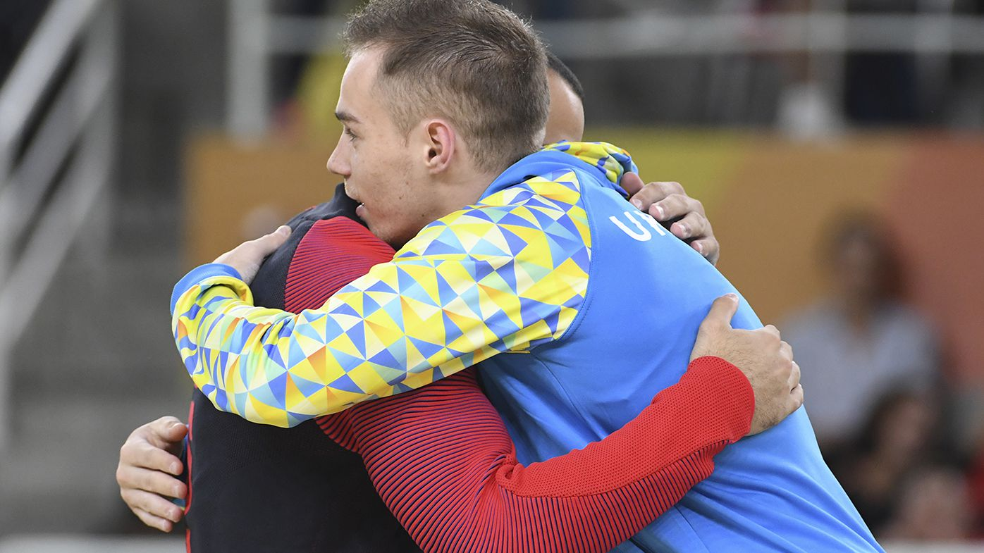 American gymnast Danell Leyva embraces Ukrainian Oleg Verniaiev who denied him the gold medal in the parallel bars. (AFP