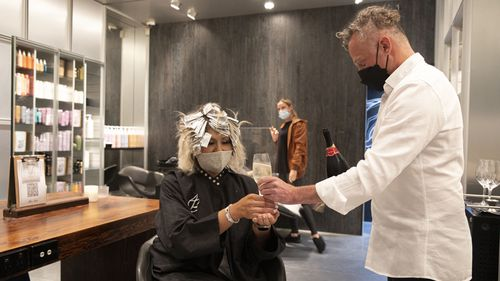 Hairdresser Alan Buki of Alan Buki Hair offers a client a glass of champagne at midnight in his Paddington salon.