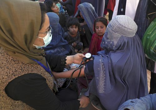 Internally displaced Afghan women from northern provinces, who fled their home due to fighting between the Taliban and Afghan security personnel, receive medical care in a public park in Kabul earlier this month.