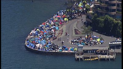 Tents, camp chairs and picnic blankets have been squeezed into popular Sydney Harbour-side spots. (9NEWS)
