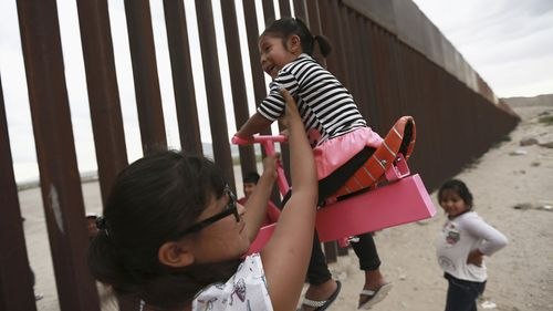 A see-saw installed using the border fence between Sunland Park, New Mexico, and Ciudad Juárez, Mexico.