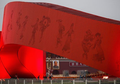 Workers set up near a red ribbon decoration on Tiananmen Square in preparation for the parade for the 70th anniversary of the founding of the People's Republic of China, in Beijing.