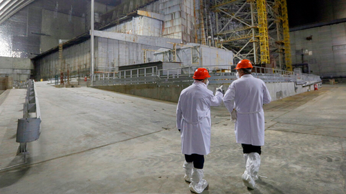 Workers walk past the covered exploded reactor inside a shelter construction at the Chernobyl nuclear plant, in Chernobyl, Ukraine.