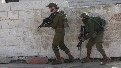 Israeli soldiers conduct a search for suspects of a shooting attack yesterday in the West Bank City of Ramallah,