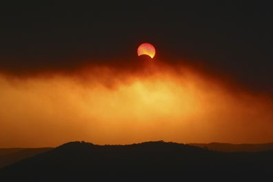 A partial solar eclipse through plumes of smoke over Broken Bay in New South Wales in 2002.