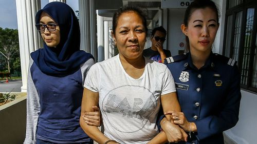 Australian Maria Elvira Pinto Exposto is escorted by Malaysia Customs officer outside the magistrate court in Sepang. (AAP)