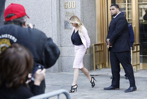 Head down,  the former adult movie star leaves court with a bodyguard (AAP)