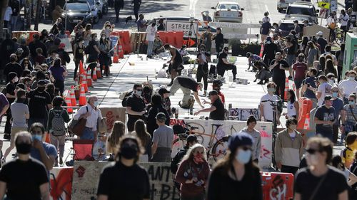 """In this June 11, 2020, file photo artists paint large letters that read """"Black Lives Matter"""" painted on a street near Cal Anderson Park inside what is being called the """"Capitol Hill Autonomous Zone"""" in Seattle"""