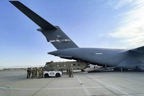 In this image provided by the Department of Defense, a CH-47 Chinook from the 82nd Combat Aviation Brigade, 82nd Airborne Division is loaded onto a U.S. Air Force C-17 Globemaster III at Hamid Karzai International Airport in Kabul, Afghanistan, Saturday, Aug, 28, 2021. (Department of Defense via AP)