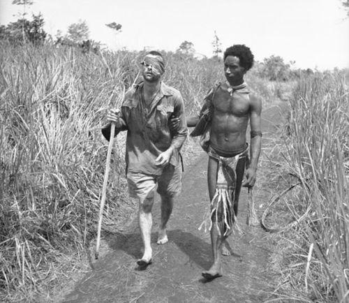 Dick Whittington being helped along a track toward a field hospital in Dobodura on 25 December 1942. (Australian War Memorial)