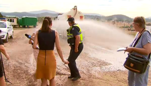 After giving the reporters a honk, the driver sprayed them. (9NEWS)