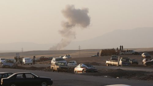Smoke rises after airstrikes targeting Islamic State militants near the Khazer checkpoint outside of the city of Irbil in northern Iraq, Friday, Aug. 8, 2014. (AP Photo/ Khalid Mohammed)