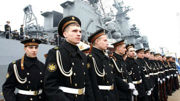 Russian sailors in front of the guided-missile cruiser Varyag, which is part of the Russian fleet north of Australia. (AAP)
