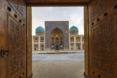Blue domes of the Madressa through open wooden door in Bukhara, Uzbekistan.