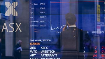 Pedestrians are reflected in a window with an indicator board displaying stock prices at the Australian Stock Exchange (ASX) in Sydney