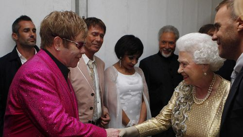 Queen Elizabeth II meets Sir Elton John backstage at The Diamond Jubilee Concert outside Buckingham Palace, London in 2012. (AAP)