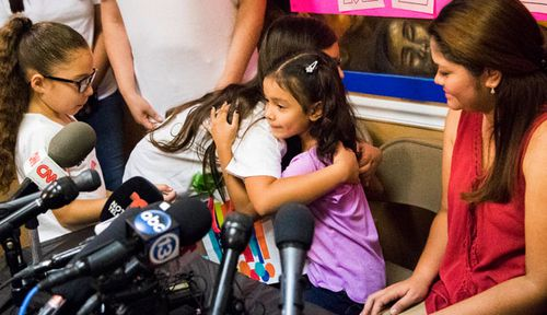 Alison Madrid 6, (purple top) embraces family members as her mother Cindy watches on. (Photo: AP).
