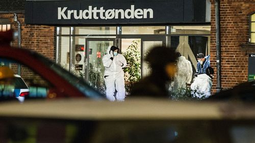Forensic experts investigate the scene in front of the cafe Krudttoenden. (AAP)