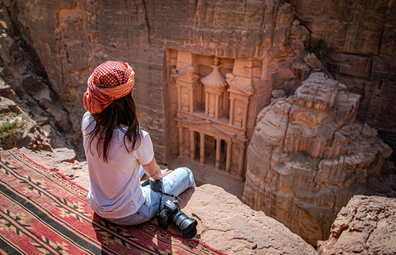 Woman sits and views Petra, Jordan from cliff