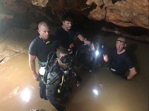 AFP divers in the dark and murky waters of the cave system.