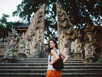 Young woman on holiday in Bali, visiting temples