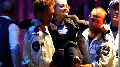 A hostage is carried out after police storm the cafe. (AAP)