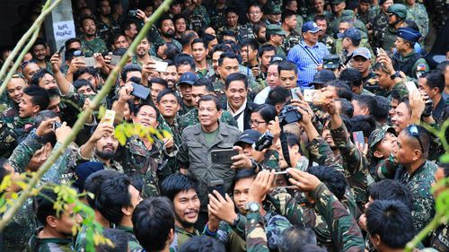 Rodrigo Duterte poses for selfies with many soldiers at once. (AAP)