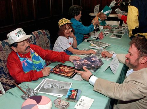 Jerry Maren, as a member of The Lollipop Guild, signs autographs as his wife Elizabeth looks on. Picture: AAP
