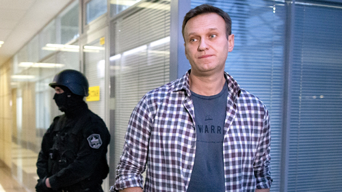 n this Dec. 26, 2019, file photo, Russian opposition leader Alexei Navalny speaks to the media in front of a security officer standing guard at the Foundation for Fighting Corruption office in Moscow, Russia.
