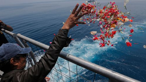 A man throws a handful of flower petals into the Java Sea where 189 people were killed.