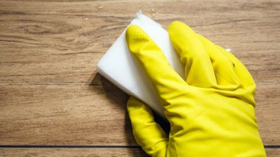 A hand in a yellow rubber glove cleaning with a magic eraser