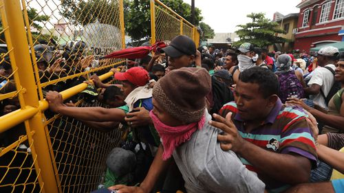 Central American migrants argue with police through a border crossing barrier at the Guatemalan town of Tecun Uman.