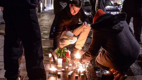 Mourners light candles outside the French embassy in Stockholm in Sweden to support victims of the Charlie Hebdo attack. (AAP)