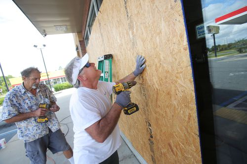 Jones (front) and Dan Steele board up a gas station in preparation for Hurricane Michael in Panama City, Florida