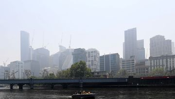 A boat motors down the Yarra River in Melbourne, Friday, January 3, 2020. A smoke haze has drifted over the city from the bushfires in East Gippsland